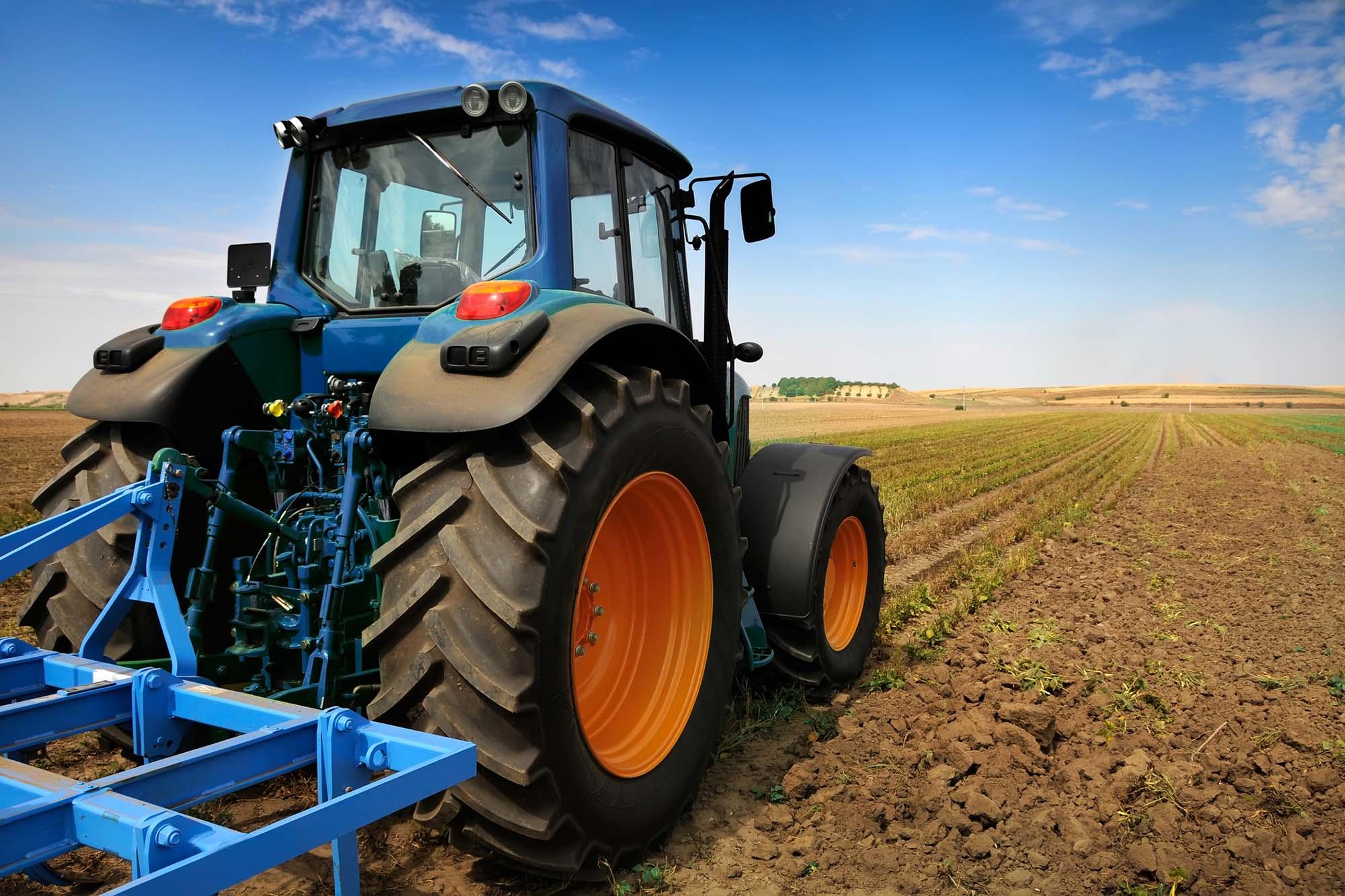 Blue tractor in muddy field