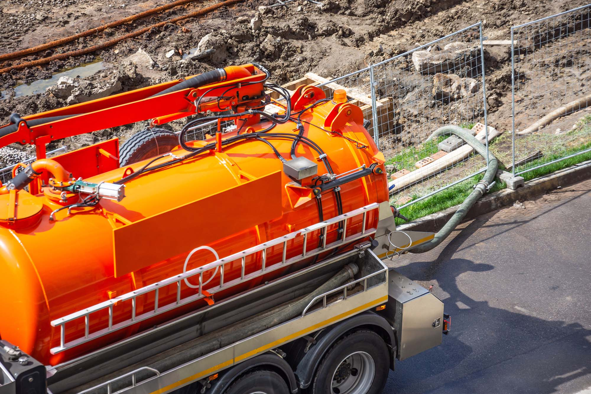 Orange Septic Tank Cleaning van cleaning building site